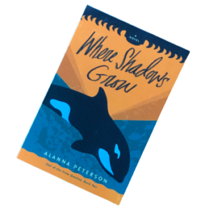 vinyl sticker of where shadows grow cover. an orca whale dives into a turquoise ocean beneath an orange sunset.